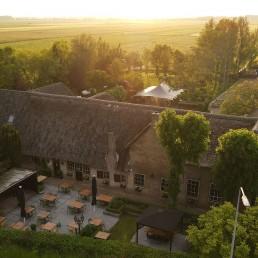 luchtfoto van de boerderij waarin Brasserie Oostgaag gevestigd is midden tussen de weilanden en in de polder van Midden-Delfland