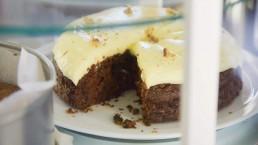 zelfgebakken chocoladetaart met 1 stuk uit de taart in een koelvitrine bij Bij de Buurvrouw
