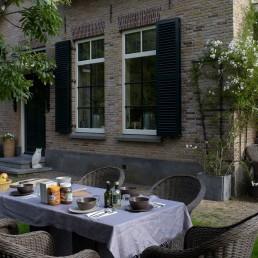 tuin van buitengoed De Uylenburg in Delfgauw met een gedekte ontbijttafel naast een oude boerderij