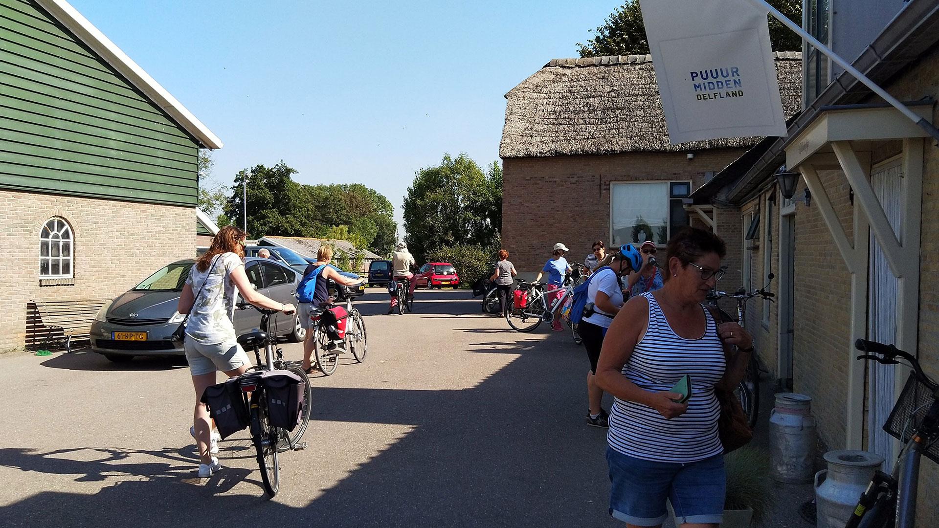 deelnemers aan de fietsroute van Fietsen voor m'n eten staan met de fiets op het boerenerf buiten de winkel van Zuivelboerderij van Winden in Midden-Delfland