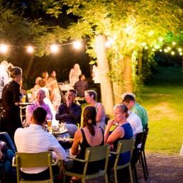 groep jonge mensen zitten 's avonds in kringetjes te praten in de tuin van Vijverschie te praten verlicht door slingers met lampjes in midden-delfland