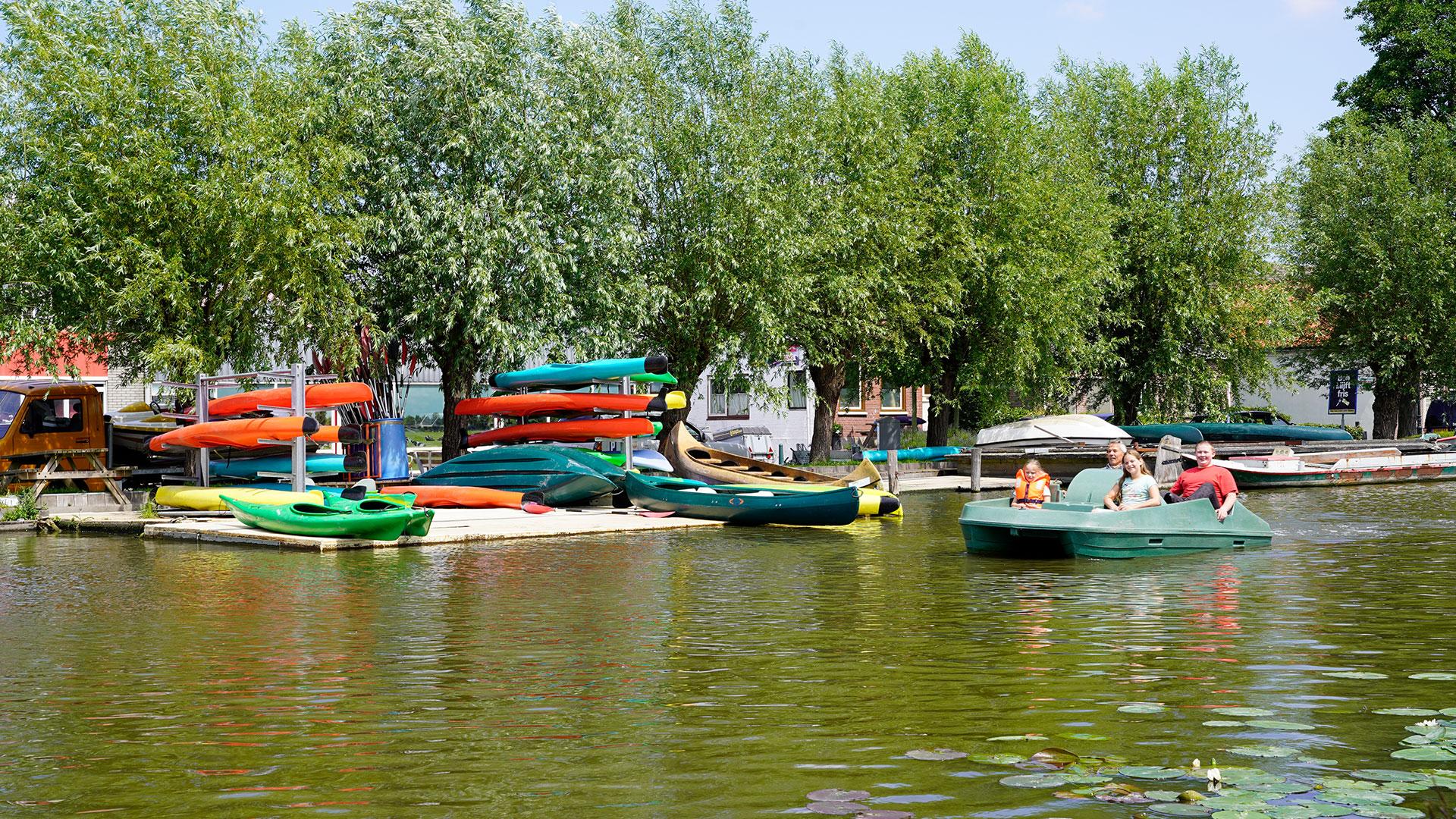 drie mensen in een groene waterfiets met in de achtergrond felgekleurde kano's op de kant voor de verhuur door Kanoverhuur Schipluiden in Midden-Delfland
