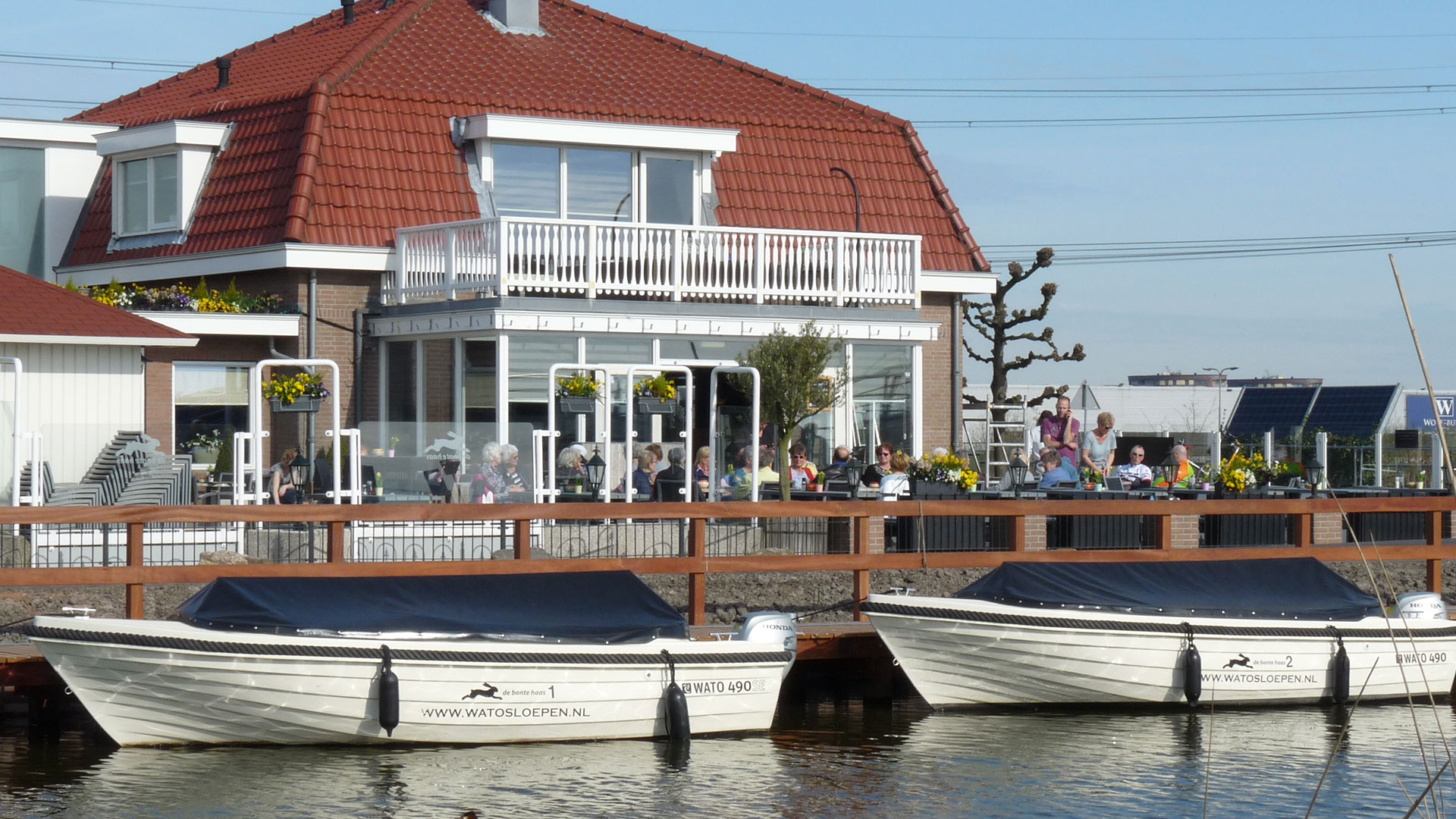 foto van het terras van eetcafe de bonte haas en de huursloepen die voor het terras in het water liggen in het Westland