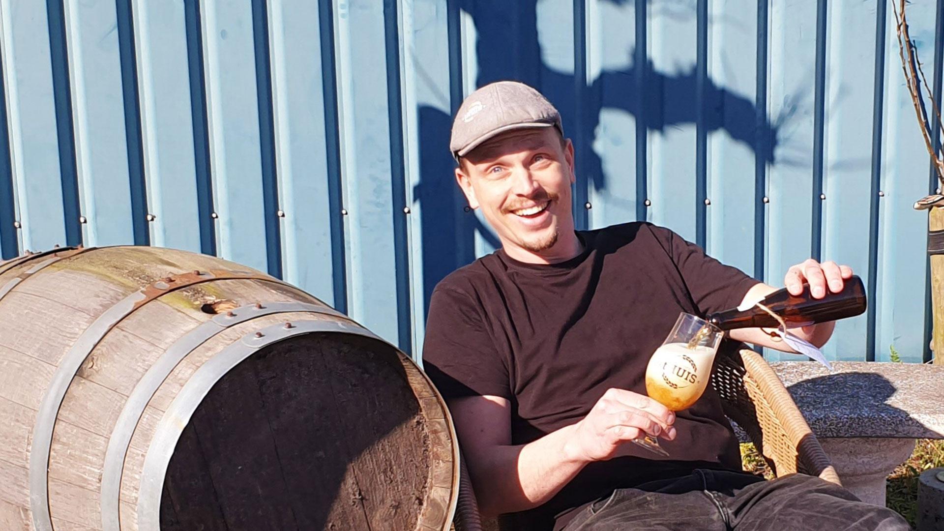 eigenaar Mark zit op het terras een biertje van zijn eigen ambachteljike brouwerij tHuis in te schenken in Midden-Delfland